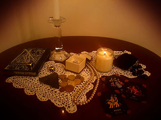 A table covered in coins, jewelry, and tarot cards lit by candlelight.