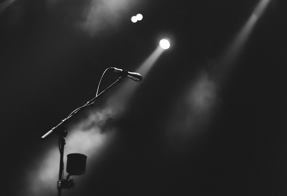 A black and white image of a microphone in a spotlight.