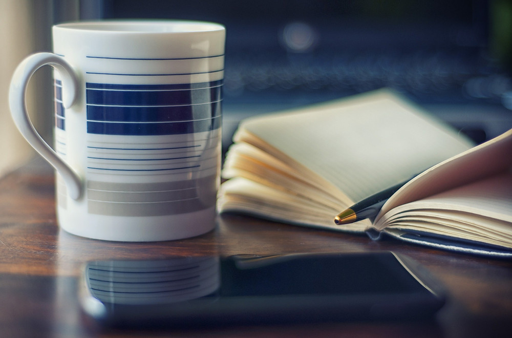 A coffee mug sits beside an open notebook with a pen resting on it on a wooden desk.