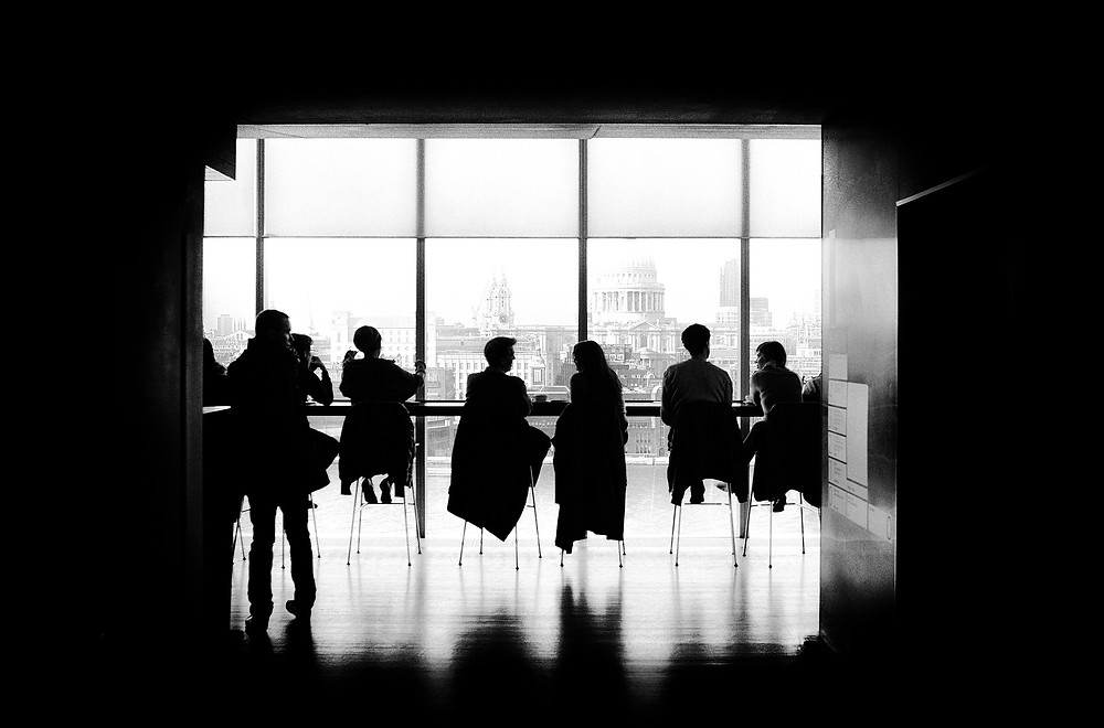 A black and white image of people sitting in front of and facing a floor-to-ceiling window that looks out on a city.