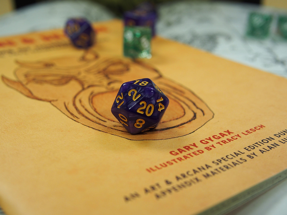 A 20-sided dice sits on a Dungeons and Dragons player book. The 20 face is facing the camera.
