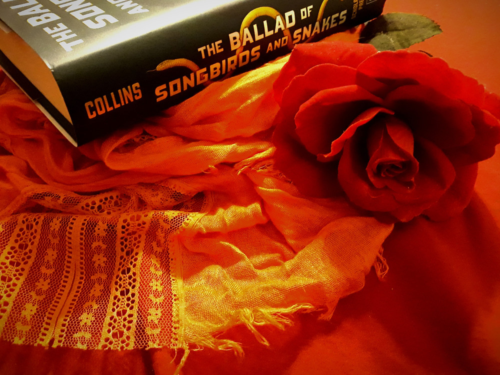 A picture of a hardcover copy of The Ballad of Songbirds and Snakes sitting on an orange scarf next to a red rose, on a red background.