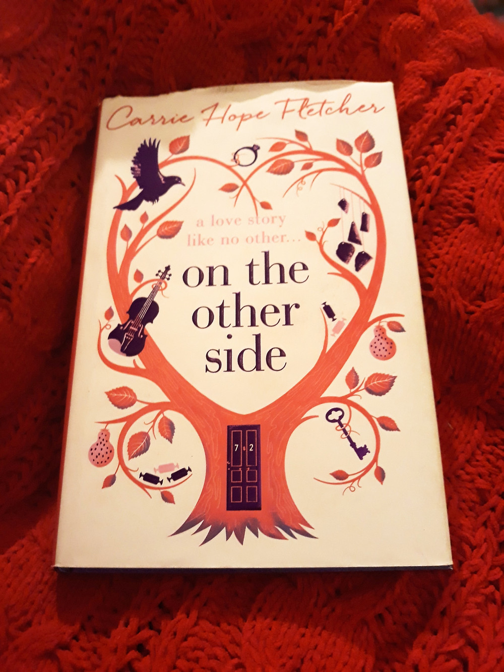 A hardback copy of On The Other Side on a red background.
