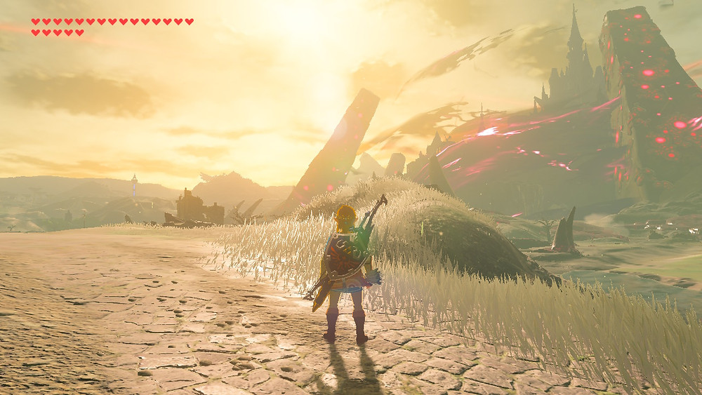 A screenshot of The Legend of Zelda: Breath of the Wild. Daytime. Link stands on a brick road with his back to the camera, facing a corruped Hyrule Castle on his right.