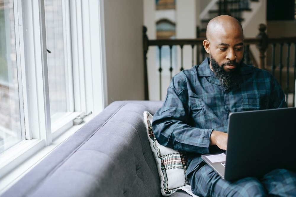 A beginner's guide to trademark infringement. A man sitting on a sofa working on his laptop.