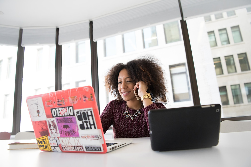 Female entrepreneur. Start a business from scratch. Woman with laptop and tablet in an office speaking on her mobile.