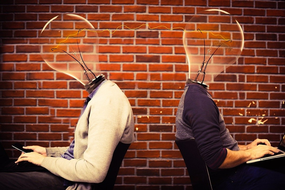 Defining a new product development process. Two people sitting away from each other with lightbulb heads.