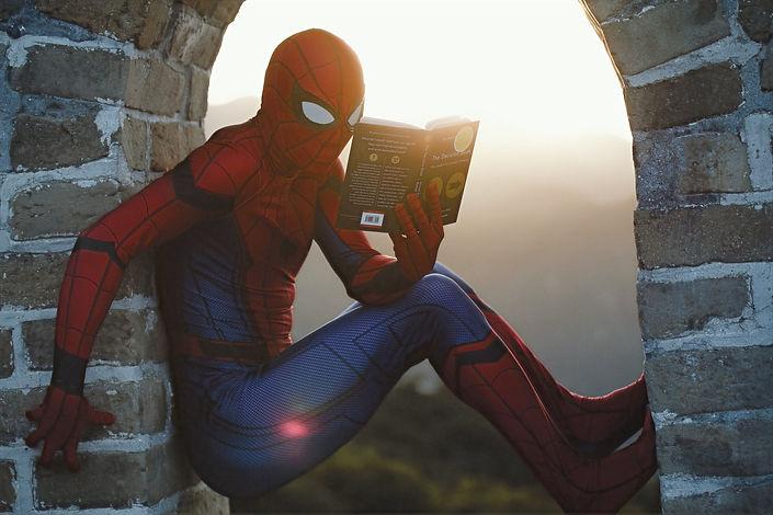 Spider-Man lehnt sich an eine Ziegelwand an und liest ein Buch