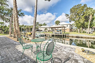 Vacation Rental Live Bait two chairs small table on dock by canal