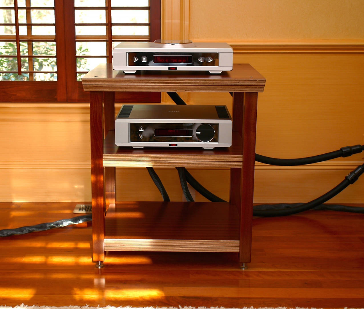 As you will see from the photos- my system is quite simple. Rega Isis cd player and Osiris integrated amplifier, Kubala Sosna Elation balanced interconnects and speaker cables, Stage III Kraken power cords, a dedicated electrical circuit with an audiophile outlet, Synergistic research acoustic art system on the walls and floor and the Magico Q1s. Prior to your rack, the components were on a piece of furniture. So this is my first experience with a proper rack in my home. All I can say is wow, what an impact it has had! Of course the rack is absolutely stunning, and the african sapele works very well with the color palette in the room. But the aesthetics are only so important. The music is simply glorious. More tonally accurate, immediate and with incredible extension. Recording locations become palpable. Instruments and vocals seem that much more realistic. Dynamics are phenomenal. I get it now. I'm glad I made the investment. So I just wanted to thank you and your colleagues for providing such a terrific product. I will cherish the rack for years. I snapped a few photos that I will send along. Not sure if it will take a few emails to get to you.  Robert M. Brenner, M.D.