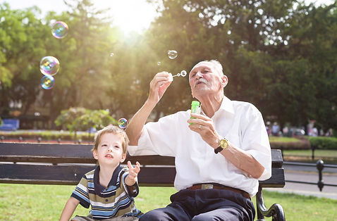 grandfather blowing soap bubbles to his