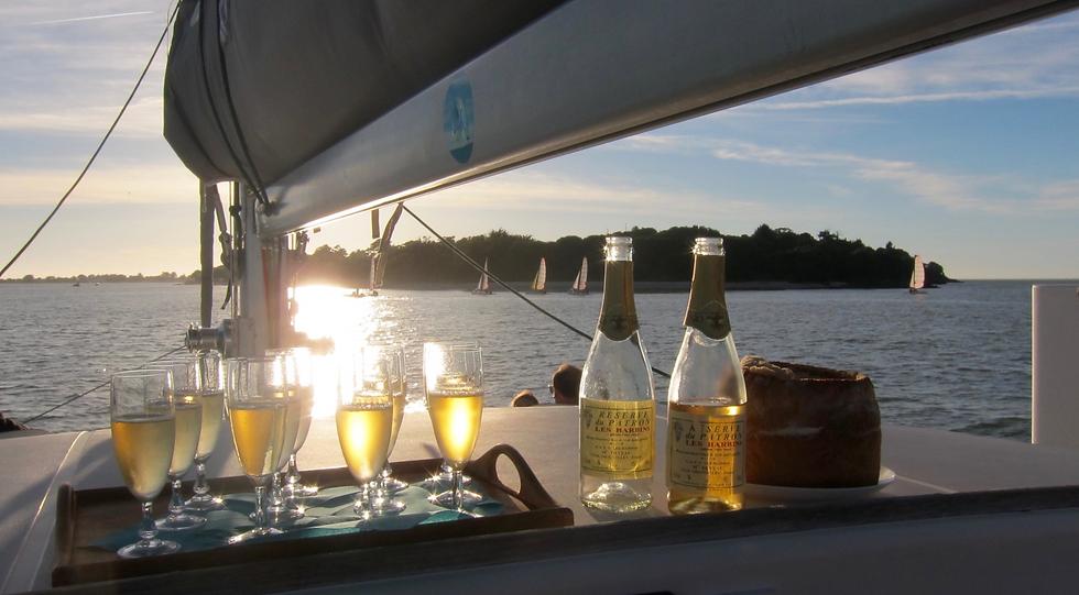 Apéro sur un bateau de soirée avec le coucher de soleil.
