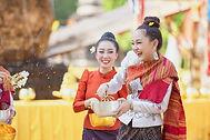 Thai girls and Laos girls splashing water during Songkran festival, Buddha statue water ce