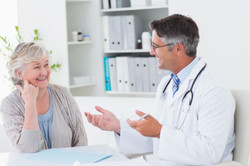photodune-10386015-happy-male-doctor-discussing-with-senior-patient-at-table-in-clinic-l