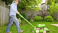 Man using a green cute lawn mower.jpg