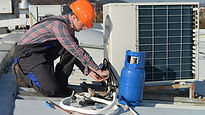 Man with orange hard hat repairing air c