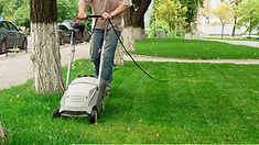 Man using a simple handheld lawn mower.j