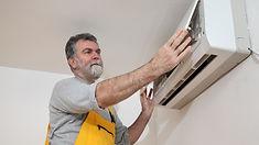 Man examining the air conditioning unit.