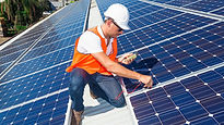 Roofer measuring solar panel temperature