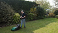 Man in black shirt using his lawn mower.