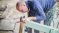 Handyman in blue shirt fixing the garage