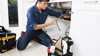 Plumber working on kitchen sink.jpg