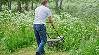 Man in white shirt  using a lawn mower.j