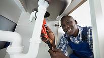 Black man doing kitchen sink plumbing.jp