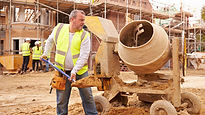 Construction worker in green vest holdin