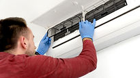 Man in red suit checking AC filter.jpg