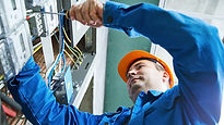 Electrician in blue overalls with orange