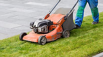 Man using an orange lawn mower.jpg