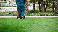 Man in blue overalls working on the lawn