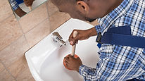 Black man fixing faucet.jpg