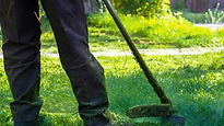 Man in black pants mowering the lawn.jpg