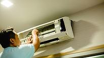 Man in blue shirt installing air conditi