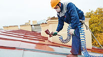 Man in spray painting the roof.jpg