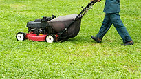 Man in his work wear using red lawn mowe