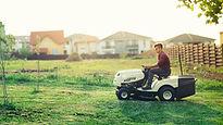 Man riding his white lawn mower.jpg