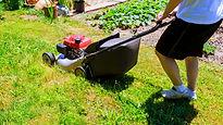 Man in white shirt using his lawn mower.