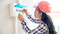 Female electrician working on fuse box.j