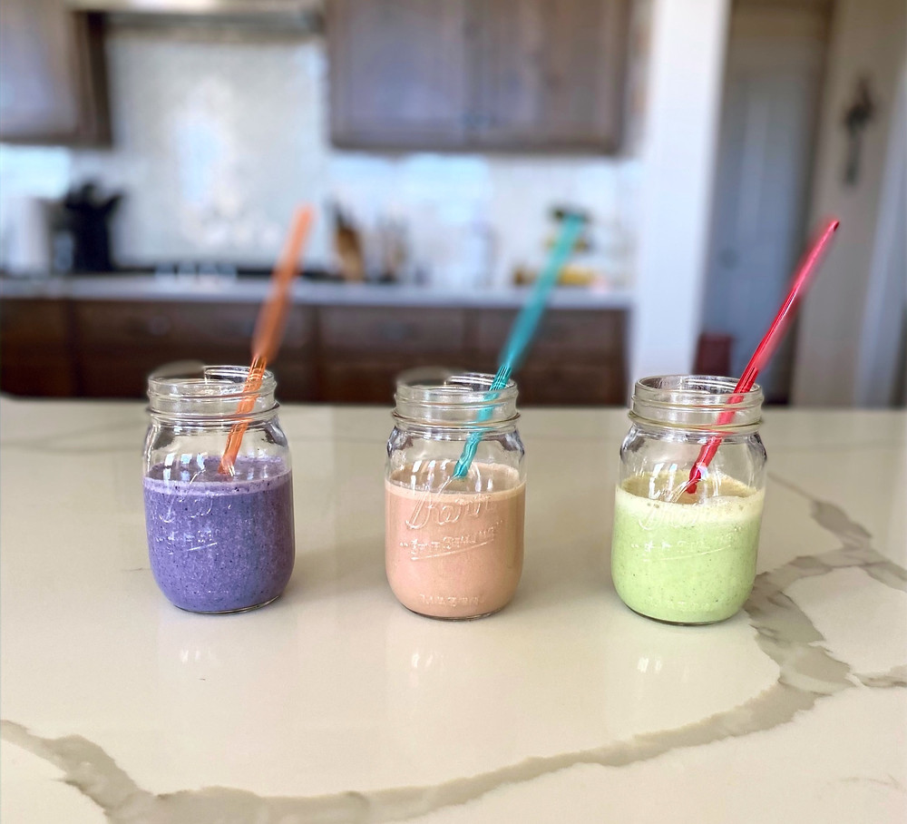 Three cups filled with various smoothies and straws on kitchen counter