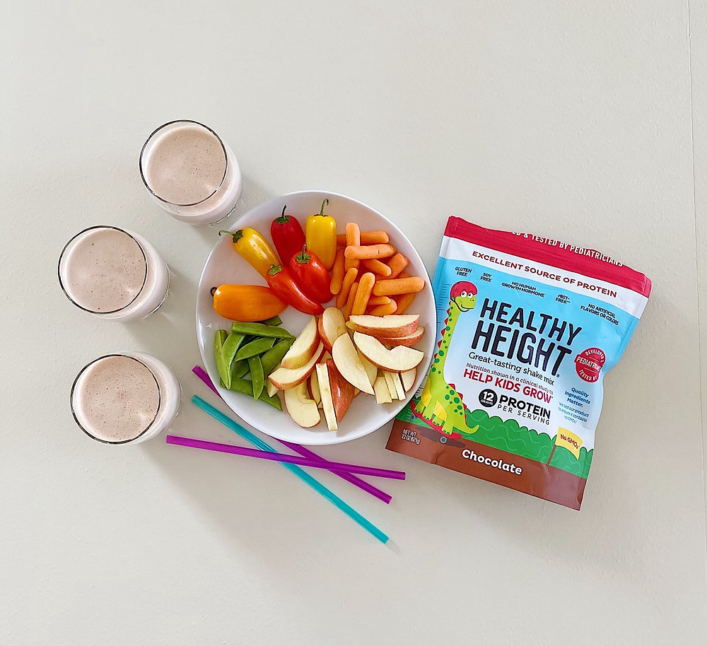 Three cups of chocolate smoothie next to plate of fruit and vegetables and a bag of Healthy Height powder mix
