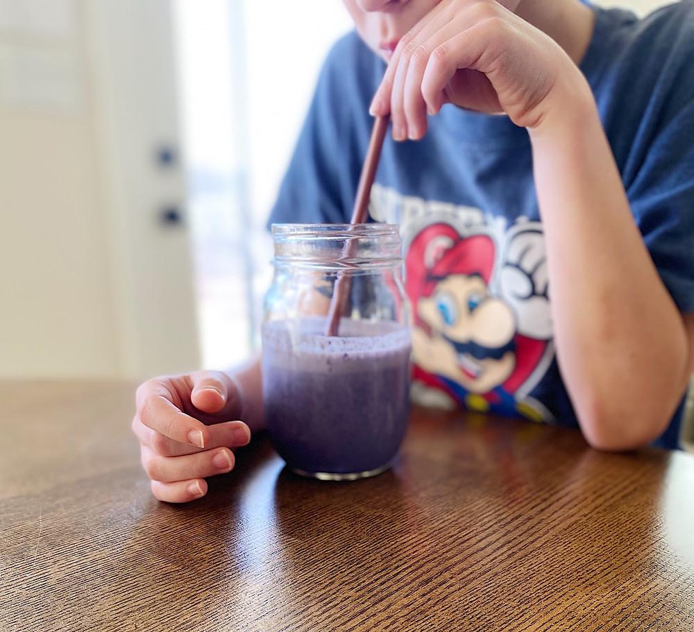 Child drinking purple smoothie with straw