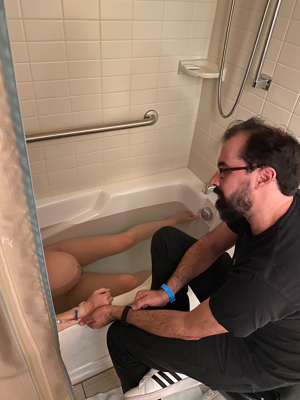 Dad supports mom through contractions in tub.