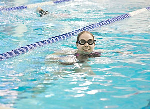 Click here to read Mae's story. Image of Mae swimming shown.