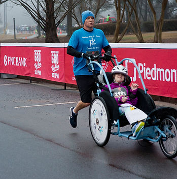 Image of Kyleign in a running wheelchair with someone pushing her in a race.
