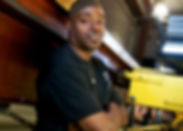 Click to hear employment stories. Image of a mechanic shown.