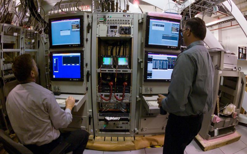 Technicians test systems in the Space and Naval Warfare Systems Center Atlantic's Common Submarine Radio Room (CSRR) production area. The curved design of the facility mimics the hull designs of four Navy submarine types, which allows for streamlined integration before systems are installed aboard the subs, and reduces cost and installation time.