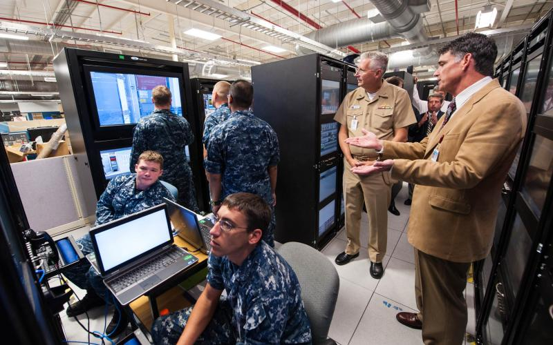 During a recent visit to South Carolina, Rear Adm. David Lewis, USN, commander of Space and Naval Warfare Systems Command (SPAWAR), looks in on sailors undergoing training at a Common Submarine Radio Room (CSRR) Multipurpose Reconfigurable Training System (MRTS).
